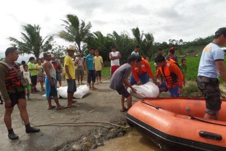 A handout picture provided by Philippine Airforce Pubilc Information Office (PAF-PIO) shows airforce rescuers unloading sacks of relief goods from a rubber boat at the bank of the swelling river in the town of Kawayan, Philippines, on Oct 18, 2015.