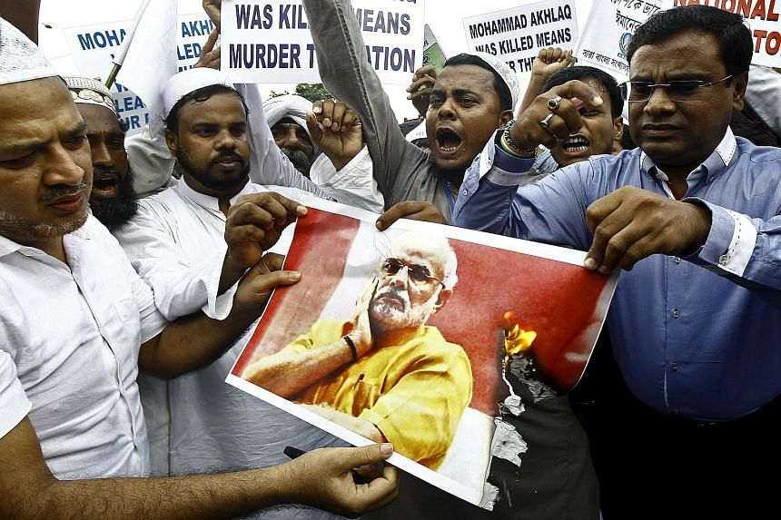 Demonstrators burning a portrait of PM Narendra Modi during a protest in Kolkata, India, on Wednesday. In his response to the murder of a Muslim man over rumours he ate beef, Mr Modi said the federal government had little role in the incident. Many i