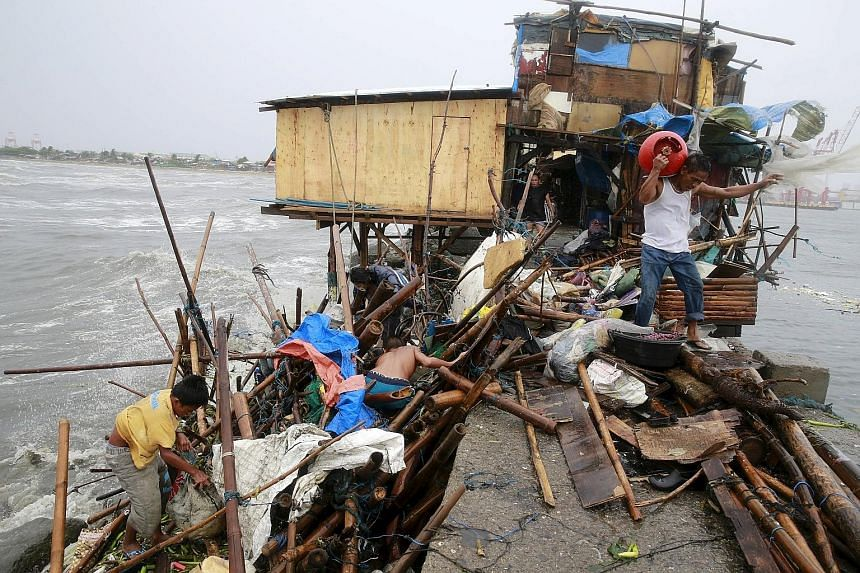 A family that lives along the coast of Manila Bay searching for salvageable items after their house was damaged by strong winds brought by Typhoon Koppu yesterday. At least eight people are missing, and a 14-year-old boy was killed when a tree fell o
