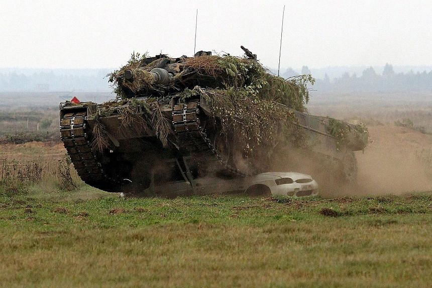 A Leopard 2 battle tank crushes a car during a Nato exercise in Poland's Masuria region last week.