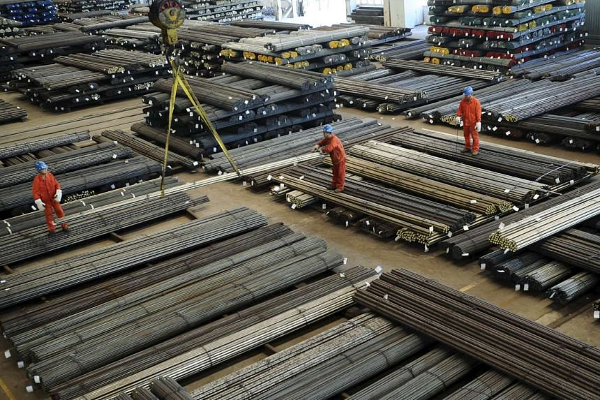 Workers direct a crane lifting newly-made steel bars at a factory of Dongbei Special Steel Group Co., Ltd., in Dalian, China.