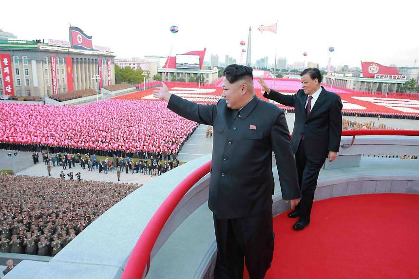 Kim Jong-un (front) waving to the crowd during a large-scale military parade to mark the 70th anniversary of the founding of the ruling Workers' Party of Korea.
