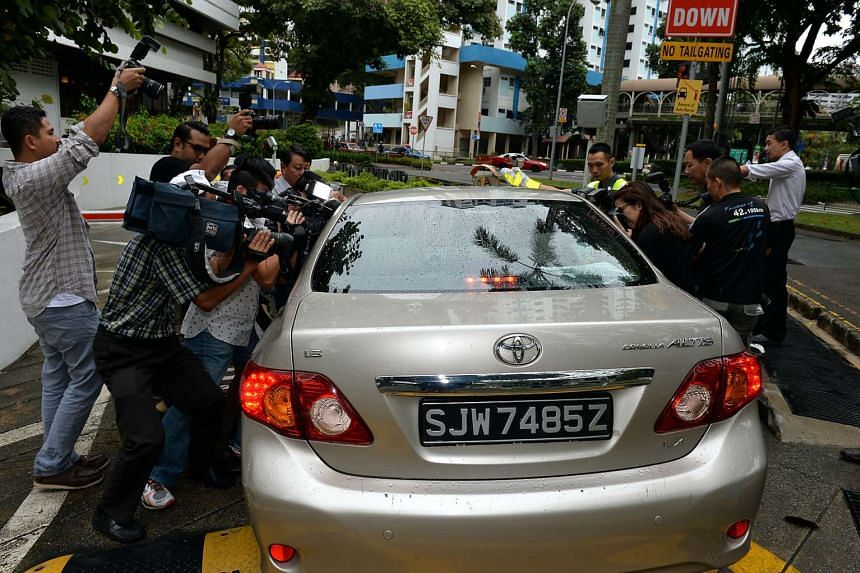Photographers and media crews scrambling to get a picture of Iskandar Rahmat as he was being escorted by police officers in a car on July 15, 2013.