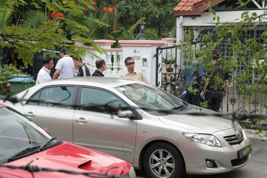 Iskandar Rahmat, who was said to have been in touch with one of his two victims, back at the crime scene with police officers on July 13, 2013.