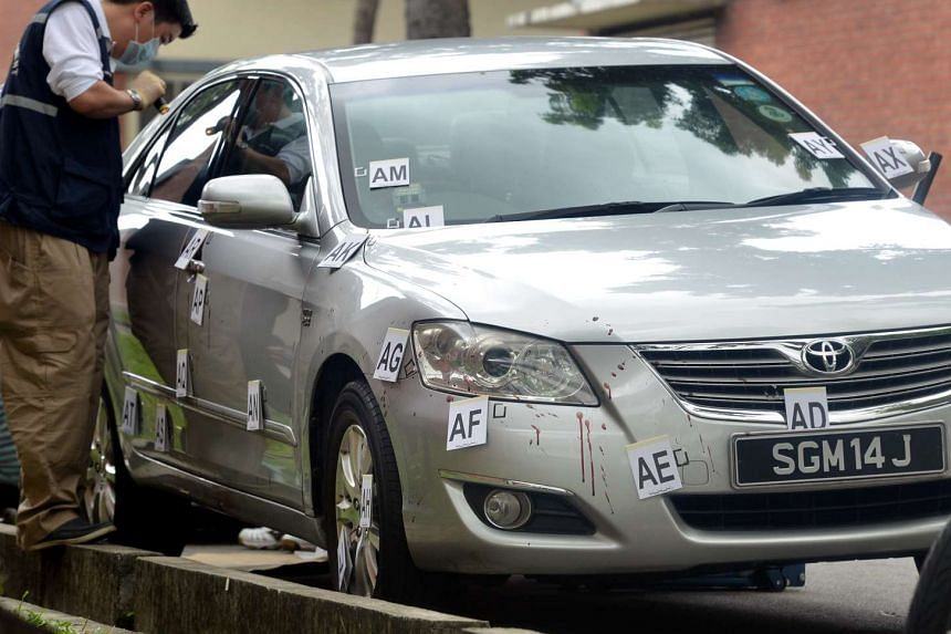An investigating officer examining the silver Toyota Camry, which was found abandoned at Eunos Ave 7.