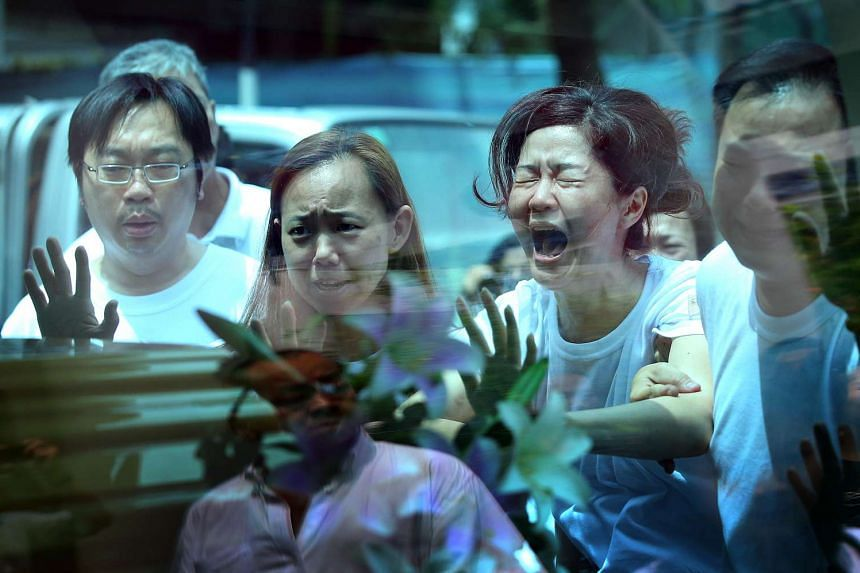 The wife of Mr Tan Chee Heong (second from right) wailing in anguish as she pushed the hearse carrying her husband's body during the funeral procession.