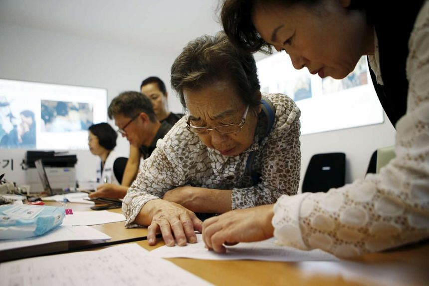 A woman who said she has family members living in North Korea gets help to prepare documents for reunion at the Red Cross building in Seoul, South Korea, on Sept 8, 2015.
