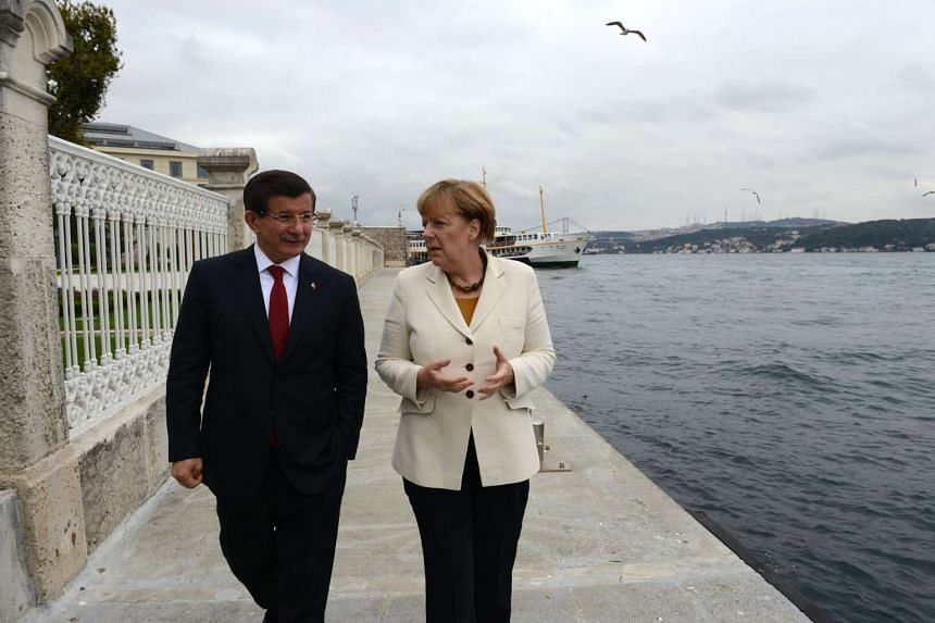 German Chancellor Angela Merkel (right) speaks with Turkish Prime Minister Ahmet Davutoglu (left) as they walk before their meeting on Sunday, in Istanbul.