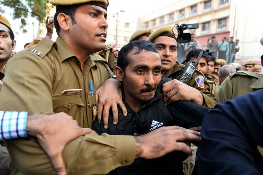 Indian police escort Uber taxi driver and accused rapist Shiv Kumar Yadav (centre) following his court appearance in New Delhi on Dec 8, 2014.