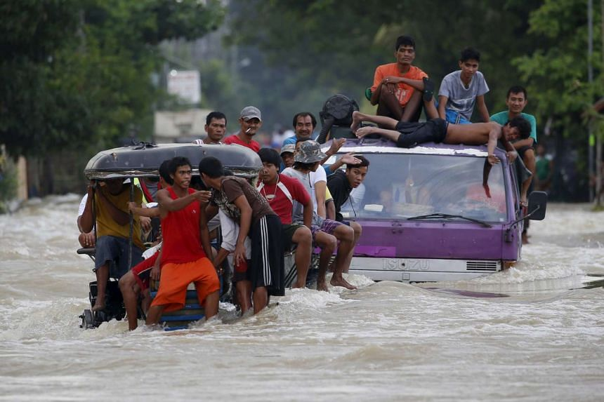 Residents ride on a truck and farm tractor amidst a strong current along a flooded highway in Zaragoza, Nueva Ecija province, in the northern Philippines, after Typhoon Koppu hit the area, on Oct 20, 2015.