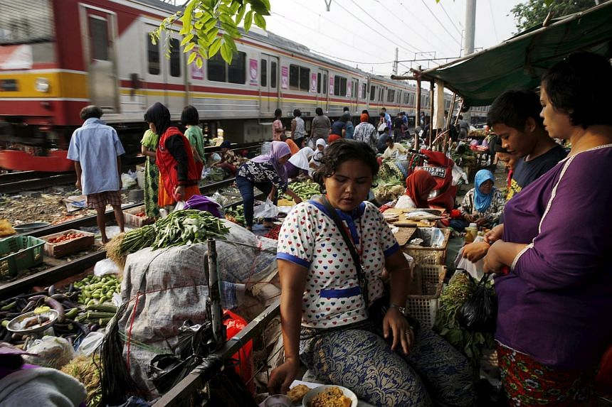 A vendor (centre) serving customers at a vegetable market as a commuter train passes in Jakarta on Oct 2, 2015.