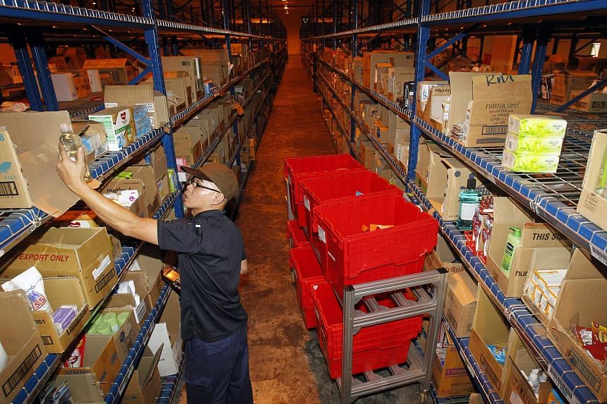 A worker picking grocery items according to customer orders at RedMart's warehouse.