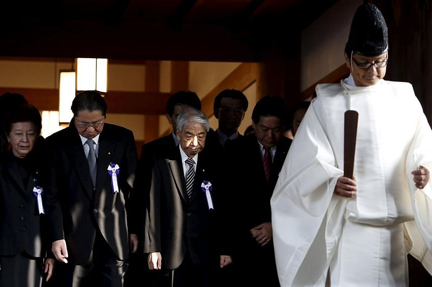 A group of lawmakers including Japan's ruling Liberal Democratic Party's Hidehisa Otsuji (third from left) are led by a Shinto priest as they pay their respects at the Yasukuni Shrine in Tokyo on Oct 20.