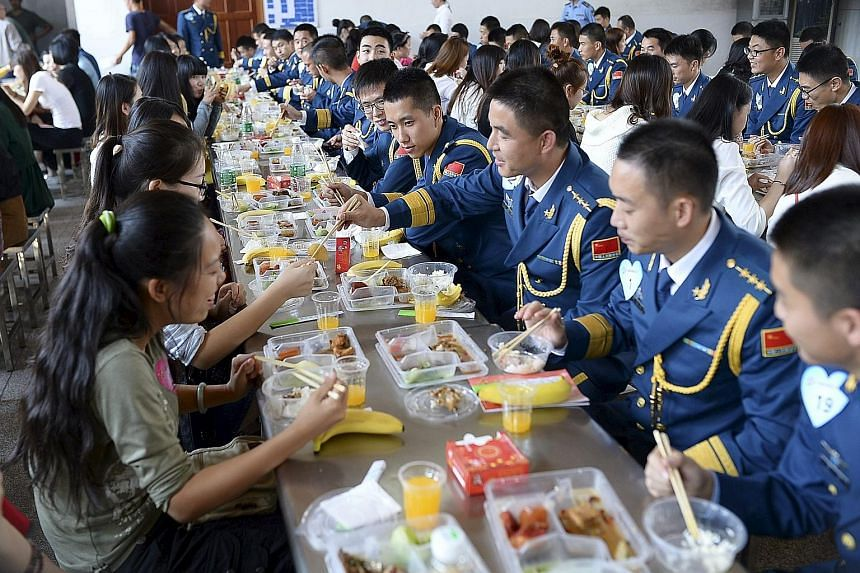 Soldiers from the Chinese People's Liberation Army air force chat with young women over lunch at a military base in Wuhan, Hubei province. More than 200 women participated in the matchmaking event last Saturday, local media reported. The government b