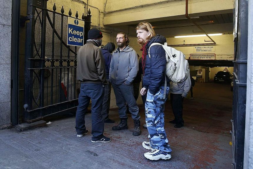Squatters at an entrance to the former stock exchange building in Manchester. Homeless people have been allowed to stay there over the winter by its owners, who include former Manchester United players Gary Neville and Ryan Giggs. The building is bei