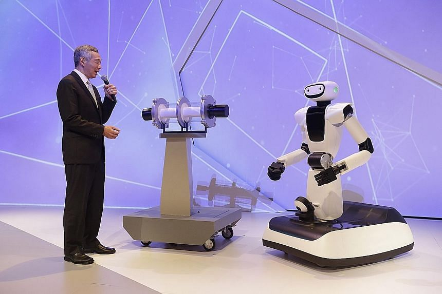 Prime Minister Lee Hsien Loong interacting with Olivia the robot, developed by A*Star's I2R, at the official opening of the $450 million Fusionopolis Two at one-north's R&D hub yesterday.