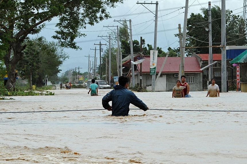 A resident holding onto a rope as he negotiates a current along a highway submerged by flood waters in Santa Rosa town, Nueva Ecija province, north of the Philippine capital Manila yesterday, a day after Typhoon Koppu hit Aurora province. Residents o