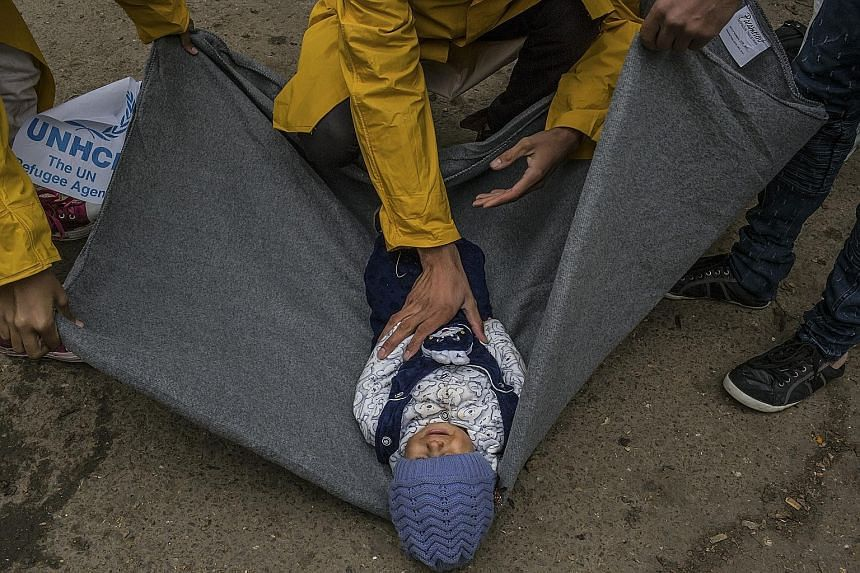 An Afghan man wraps his child in a blanket before crossing into Croatia from Serbia. With autumn winds carrying the first hints of frost, and the situation along European borders unresolved, migrants, aid workers and government officials are anxious