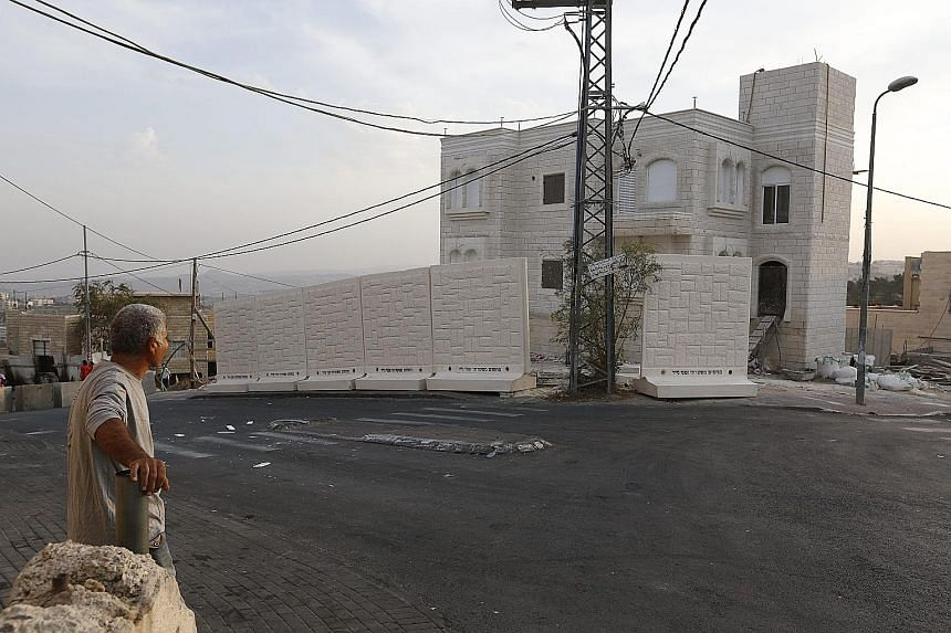 Slabs of the wall, each about 2.5m high and 2m wide, were placed by Israeli police between the Palestinian Jabel Mukaber and Jewish Armon Hanatziv neighbourhoods on Sunday.