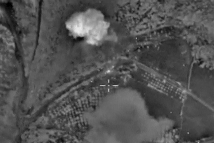 Smoke rising from what Russia says is a militant workshops near Sermania in Idlib province, Syria, after Russian planes launched an airstrike on it, in footage taken from the Russian Defence Ministry on Oct 19, 2015.