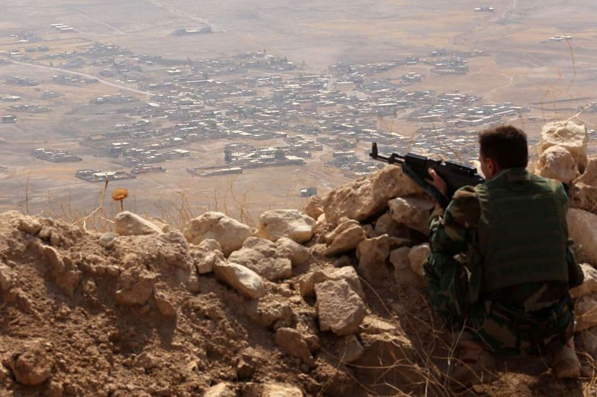 An Iraqi Kurdish Peshmerga fighter monitors his surroundings from the top of Mount Zardak, about 25km east of Mosul, on Aug 6, 2015.