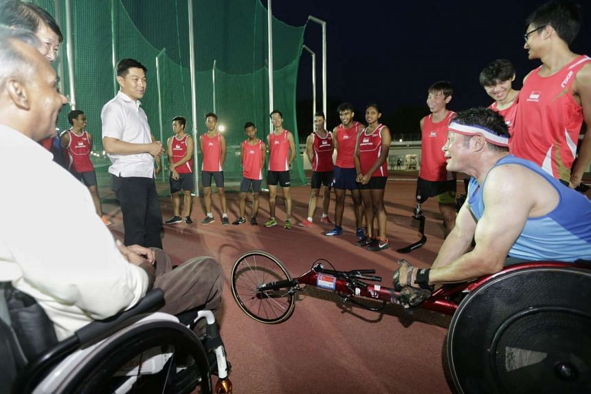 Minister for Social and Family Development Tan Chuan-Jin with para-athletes from the track and field team at the Kallang Practice Track on Oct 20, 2015.