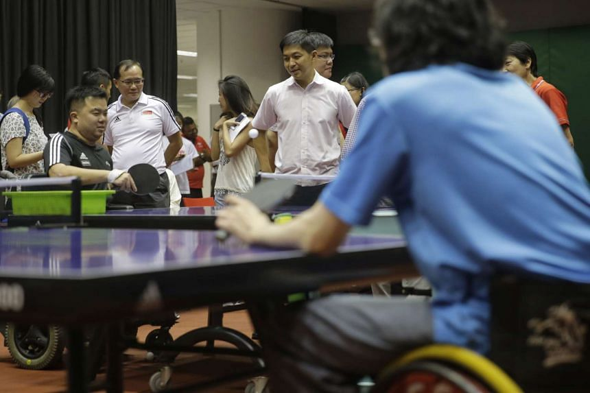 Mr Tan watching para-athlete Jason Chee, from the table tennis team, at the Singapore Sports Institute.