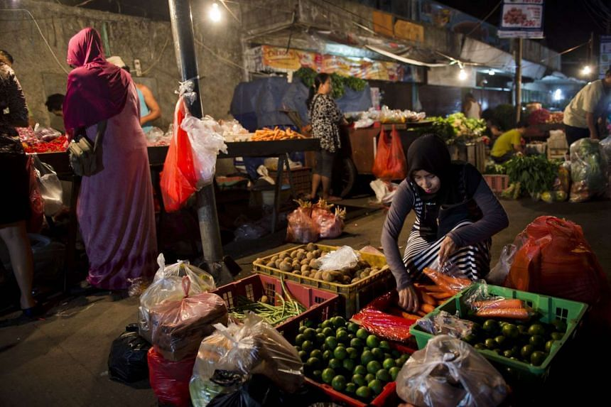 Indonesians buying food at a night market in Jakarta.