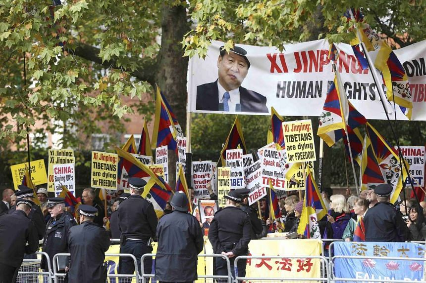 Police officers stand in front of pro-Tibet and Falun Gong protesters waiting for China's President Xi Jinping to pass on the Mall during his ceremonial welcome in London on Oct 20, 2015.