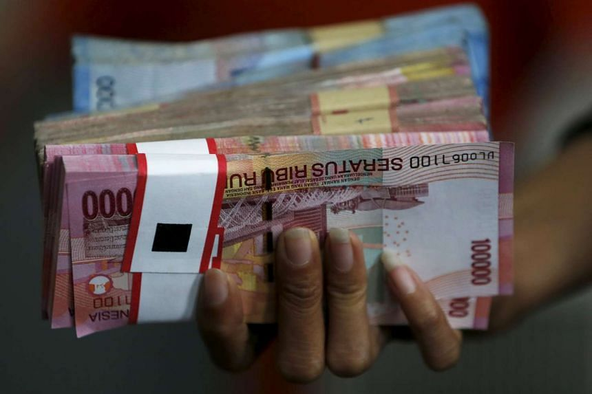 A man holding a stack of Indonesian rupiah notes.