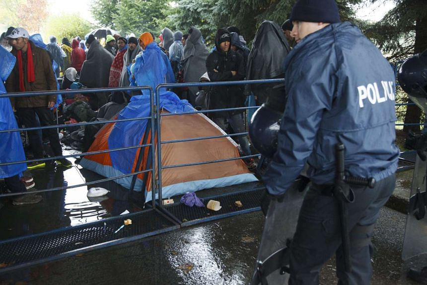 Illegal migrants wait for entry to Slovenia in the rain in front of Croatian police officers at the Croatian-Slovenian border station in Trnovec, Croatia on Monday.