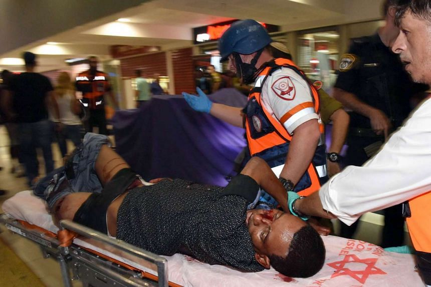 A wounded Eritrean man, who later died from his injuries, is evacuated at the main bus station in the southern Israeli city of Beersheva on Sunday, after he was mistakenly shot by an Israeli security guard and beaten by a mob following a deadly assau