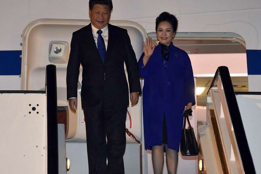 Chinese President Xi Jinping (left) and his wife Peng Liyuan, arrive at Heathrow Airport in west London on Monday, for a four-day state visit.