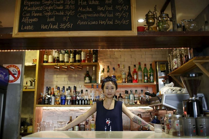Ms Ding Jia in her bar in Shanghai. College graduates like her who start their own businesses are being hailed in state media as a new creative class, with many getting training, subsidies, free office space and other support.