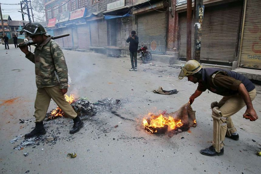 A police officer trying to put out a fire started by Kashmiri Muslim protesters during demonstrations over a trucker's death in Srinagar, Indian Kashmir, on Sunday.