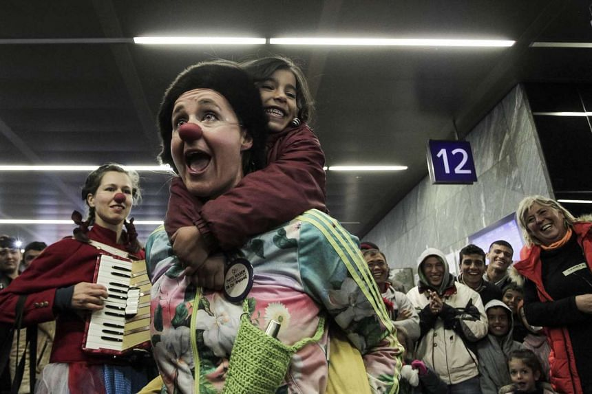 """""""Red Noses Emergency Smile Austria"""" members performing for migrants at Vienna's main train station last Thursday. The project uses 66 clowns to spread cheer among the thousands of migrants arriving in Austria daily, particularly the children."""