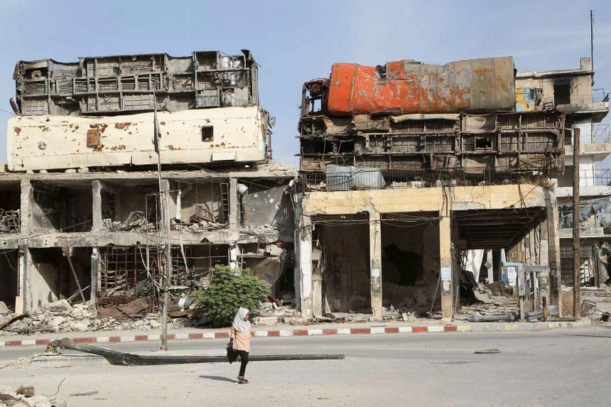 Damaged buses are positioned atop a building as barricades to provide protection from snipers deployed by the forces of Syrian President Bashar al-Assad, in the city of Aleppo on Sunday.
