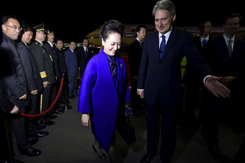 Peng Liyuan, wife of Chinese President Xi Jinping, is escorted by Britain's Foreign Secretary Philip Hammond after arriving for a four-day state visit at London's Heathrow Airport, Oct 19, 2015.