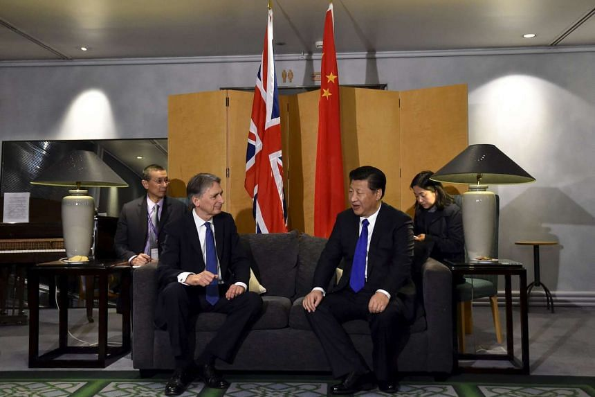 Chinese President Xi Jinping (right) talks with Britain's Foreign Secretary Philip Hammond after arriving for a four-day state visit at London's Heathrow Airport, Oct 19, 2015.
