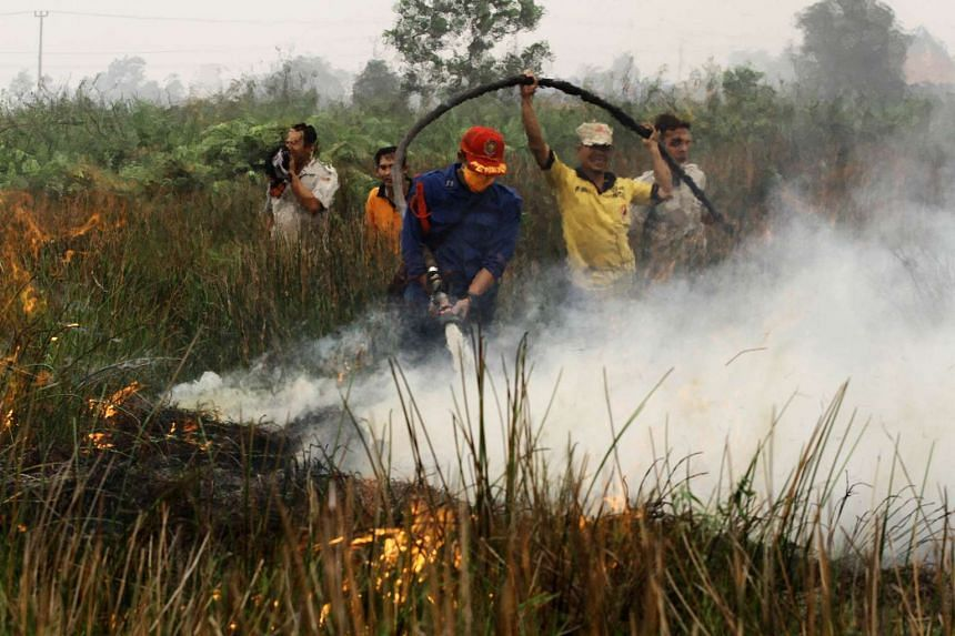 Indonesian firefighters putting out a blaze in Banyuasin, South Sumatra. Indonesia.