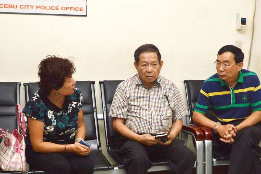 Two Chinese nationals, a consular officer (left) and her husband (right, with handcuffs), suspects in the shooting of Chinese consul general Song Ronghua at a restaurant, talk to an interpreter (centre) at a police station in Cebu City, central Phili
