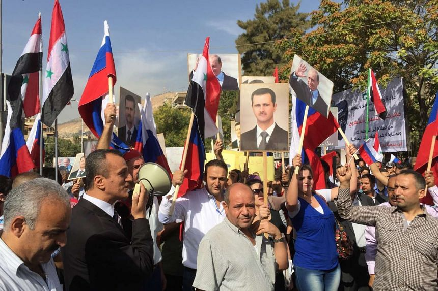 """Hundreds of Syrians gathering in front of the Russian embassy in Damascus, Syria to express gratitude to Russia for its recent military intervention aimed at eradicating ISIS and other """"terrorist groups"""", on Oct 13, 2015."""