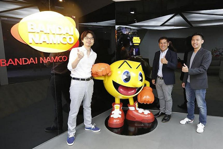 Japanese game-maker gumi Asia's Wakfu Raiders (above, left and right) was made in Singapore. Bandai Namco Studios Singapore's managing director Makoto Ishii (centre, with producer Takashi Ohwaki and senior producer Ian Pang, right) says there are pla