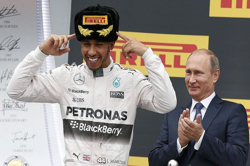 Russian President Vladimir Putin on the podium in Sochi with Lewis Hamilton on Oct 11, after the Mercedes driver clinched his second straight Russian Grand Prix. Come Sunday, the Briton will be hoping that instead of a Russian fur hat, he will be don