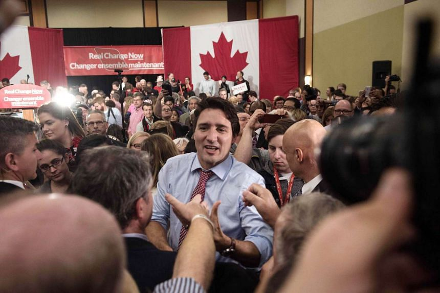 Canadian Liberal Party leader Justin Trudeau greeting a supporter at the end of his speech at a victory rally in Ottawa on Oct 20, 2015 after winning the general elections.