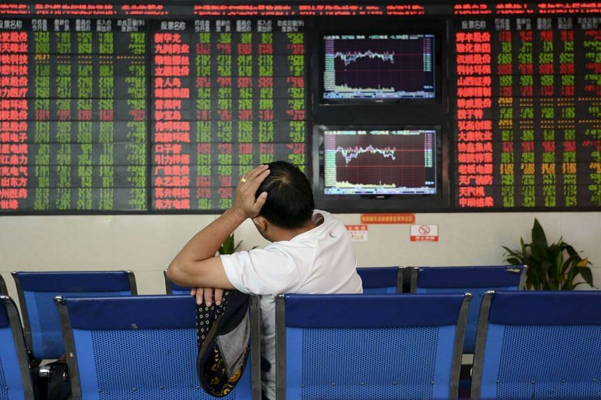 An man sitting in front of an electronic board showing stock information at brokerage house in Fuyang, Anhui province, China on Oct 14, 2015.