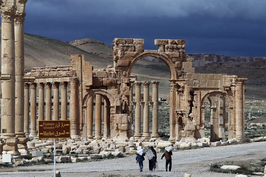 A file picture taken on March 14, 2014 shows visitors walking near the famous Arch of Triumph of the ancient oasis city of Palmyra.