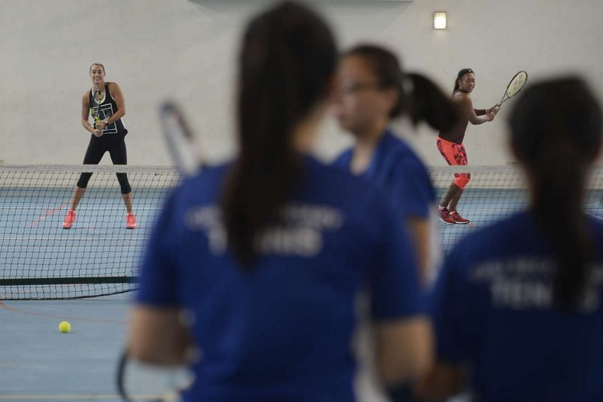 Caroline Garcia (left) and Naomi Osaka (right), training with the CHIJ Secondary School (Toa Payoh) tennis team during a visit on Oct 21, 2015.