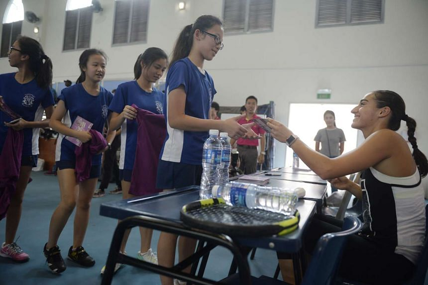 Caroline Garcia signing autographs for members of the CHIJ Secondary School (Toa Payoh) tennis team during a visit on Oct 21, 2015.