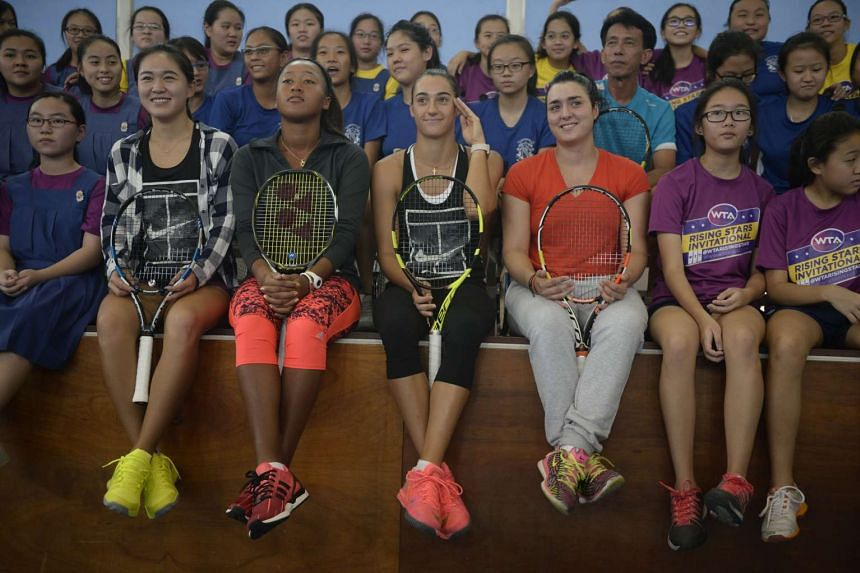 (From centre, left) Zhu Lin, Naomi Osaka, Caroline Garcia and Ons Jabeur posing for a photograoh with the CHIJ Secondary School (Toa Payoh) tennis team on Oct 21, 2015.